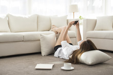 Cheerful Young Chinese Woman Using Smart Phone At Home