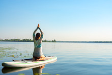 Female Practicing Yoga On A SUP Board