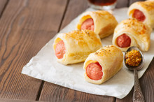 Pigs In A Planket. Puff Pastry Rolls With Sausages On A Wooden Background. Fast Food Or Beer Snack Concept.