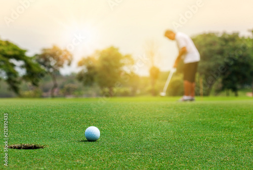 Poster Golf Golfer putting golf ball on green grass course with sunlight in morning time. Sport and recreation playground for golf club concept.