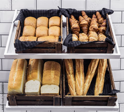 Foto op Aluminium Brood freshly baked bread and baked goods in a basket on the counter of the bakery.