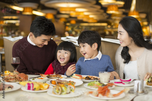 Cheerful young Chinese family having buffet dinner - 212896606