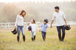 Cheerful young Chinese family walking on grassy field