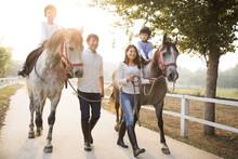Happy Family Riding Horse Outdoors