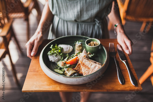 Woman hands holding plate with oriental breakfast with poached eggs, tomatoes, couscous, eggplant and spicy sauce on a wooden stand
