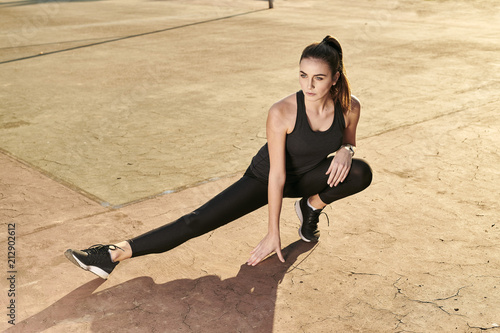 Sportive woman stretching leg on concrete floor