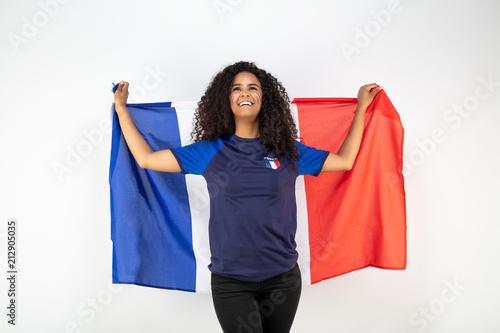 Portrait d'une jeune supportrice de l'équipe de France de football portant un chapeau , des lunettes tricolore et une écharpe de son équipe