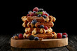 canvas print picture - freshly baked stack of belgian waffles with berries on wooden cutting board on black