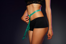 Woman Measuring Her Waist Over Dark Background  With Green Tape. Wellness Concept.