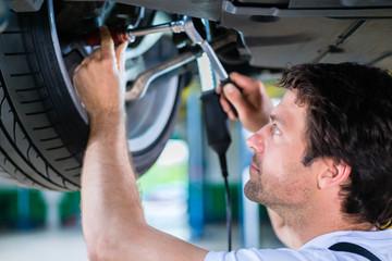 Fototapeta Mechanic working on car wheel in service workshop