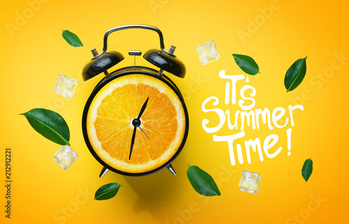 Fototapeta It's Summer Time Typography. Alarm Clock of Orange Fruit Green Leaves and Ice Cube Flying Around on Yellow Background obraz