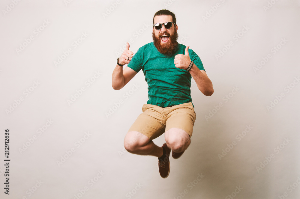 Fototapeta Cheerful bearded hipster man with sunglasses jump over white background and showing thumbs up