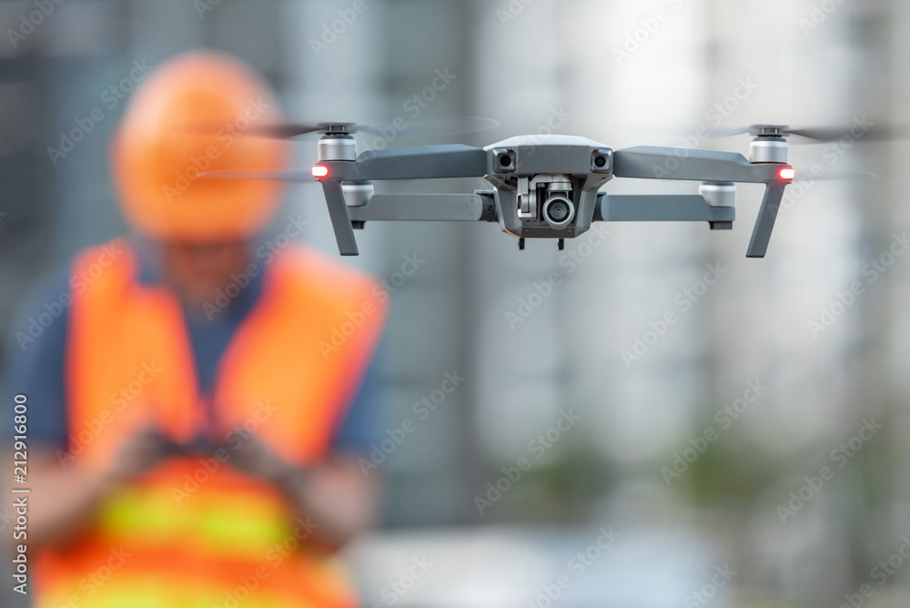 Fototapeta Young Asian engineer flying drone over construction site. Using unmanned aerial vehicle (UAV) for land and building site survey in civil engineering project.