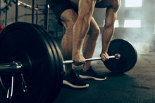 Fit Young Man Lifting Barbells Working Out In A Gym