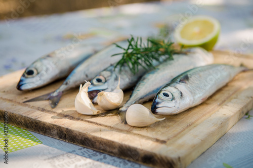 Foto op Plexiglas Vis Raw mackerel with claws of garlic and lemon on wooden plate. Fresh fish