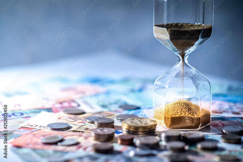 Fototapety, obrazy: Sand running through the shape of hourglass on table with banknotes and coins of international currency. Time investment and retirement saving. Urgency countdown timer for business deadline concept