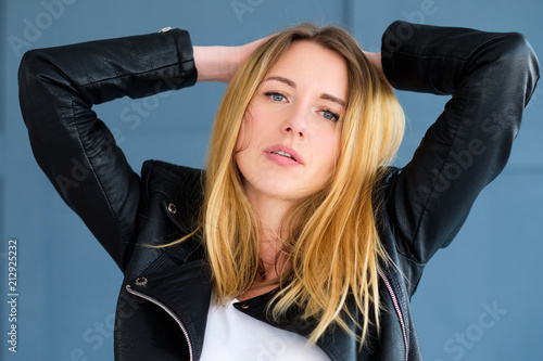 Fotografie, Obraz  disheveled sexy young woman in black leather rocker jacket with ruffled hair