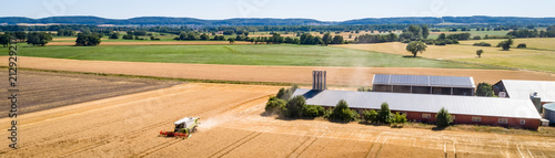 Foto  Luftbild - Getreideernte im Mittelgebirgsraum,Mähdrescher vor einer Schweinemast