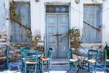 Blaue Türen An Einem Alten, Verfallenen Gebäude Mit Griechischen Kafeneion Stühlen Und Tischen Davor, Kykladen, Griechenland