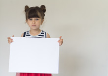 Little Girl Is Holding Blank Banner And Looks Unhappy, Isolated Over White