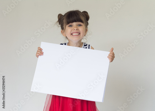 Obraz Smiling girl with white blank. Advertising place for you, empty card, cute kid holding it. - fototapety do salonu