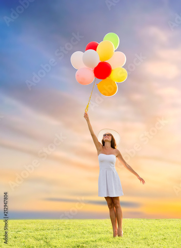 Spoed Foto op Canvas Wanddecoratie met eigen foto happiness, summer and people concept - smiling young woman wearing sunglasses with balloons on meadow over sunset sky background