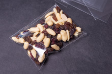 Nuts And Raisins In Cellophane Bag On Black Background