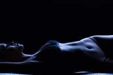 Beautiful Female Body In Blue Light In The Studio On A Black Background