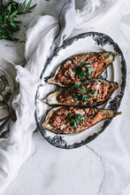 A Bolognese Sauce Served In An Eggplant Shell On A Marble Background