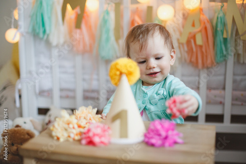 Cute Happy Little Girl Sitting At The Table With Birthday Hat One Year Old Celebration
