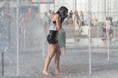 Obraz na plátně Girl bathe in the fountain in hot summer day