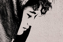 Sad Troubled Teenager School Boy With Hood On Posing Outdoor Sitting Alone On The Street - Stock Photo Made Like Graffiti Stencil Painting On White Concrete Wall