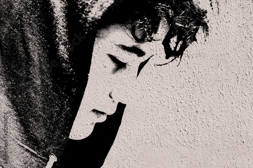 Sad troubled teenager school boy with hood on posing outdoor sitting alone on th Canvas Print
