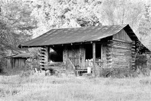 Old, Rustic Abandoned Log Cabin In Black And White. Little House Has Square Logs, Rusty Metal Roof, And Windows With An American Flag. Concepts Of Americana, Old-fashioned, Nostalgia,