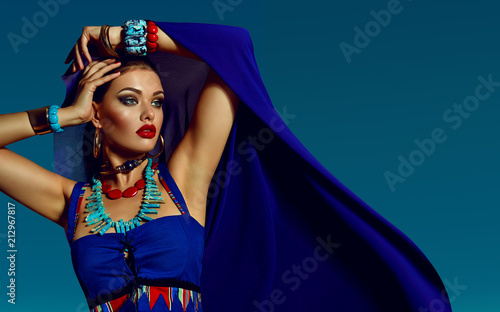 Fotografie, Obraz  beautiful young girl in bright blue attire and a lot of jewelry on the background of a bright sky