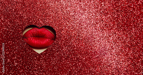 Fototapeta A girl with beautiful puffy lips, painted red lipstick with a metallic effect