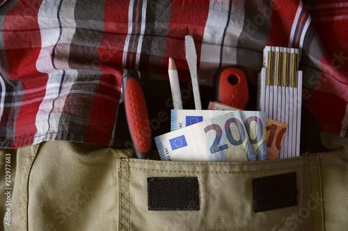 Foto  Handwerker mit Werkzeug und Geldscheinen in der Hosentasche