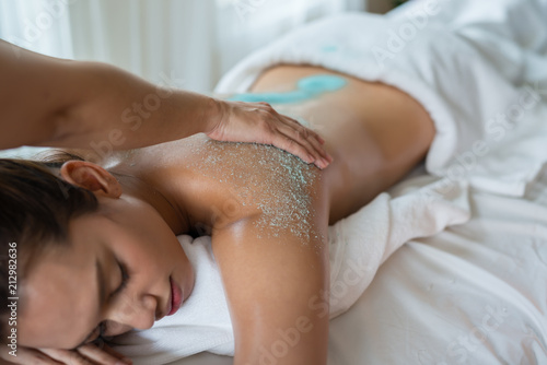 In de dag Spa Young beautiful Asian woman relaxing in the spa massage and having salt scrub massage at back. healthy lifestyle and relaxation concept. Select focus hand of masseuse.