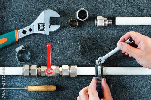 Foto op Aluminium A plumber fixes a water leak on a water pipe. Repair plumbing background.