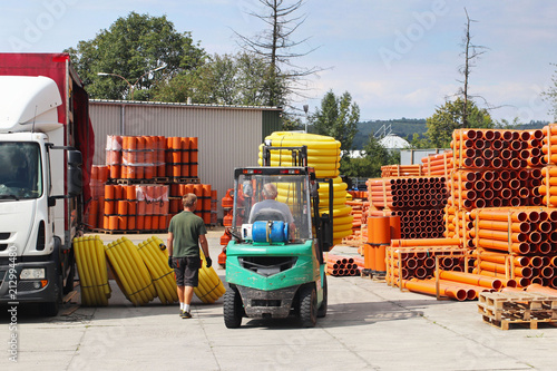 Fototapety, obrazy: Workers with forklifts in a warehouse of plastic pipes. Sale of materials for construction and upgrading of the territory. Industrial products from plastic. Making money and mechanizing heavy work.