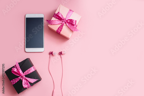 Fotografia  Smartphone, headphones and gift boxes on a pink background.