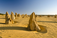 Strange Limestone Pillars Emerge From The Golden Sand Of The Pinnacles Desert In Nambung National Park, Western Australia. Lit By The Late Afternoon Sun, With Long Shadows.