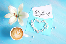 """Cup Of Cappuccino Coffee, Lily Flower, Heart And  Inscription """"Good Morning"""" On Blue Wooden Background. Concept - Morning Of Newlyweds Or Lovers, Top View, Flat Lay."""