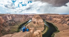 Young Couple Sitting On A Rock And Looking Over The Horseshoe Bend, Bend Of The Colorado River, King Bend, Glen Canyon National Recreation Area, Page, Arizona, USA, North America