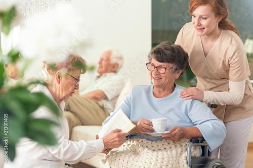 Fotografia  Two senior pensioners enjoying their leisure time together inside a private nursing home