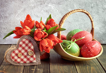 Easter Composition With Red Tulips, Wooden Heart And A Basket Of Colored Easter Eggs On Dark Rustic Wood
