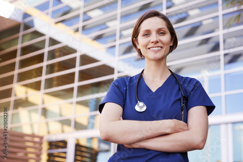 Fotografía  Smiling white female healthcare worker outdoors, waist up