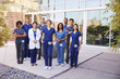 Healthcare team with ID badges stand outdoors, full length