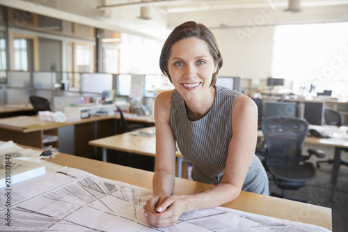 Photo Young female architect leaning on desk smiling to camera