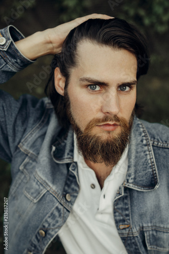 A large-sized portrait of a bearded dark-haired guy in a blue jeans similar to Canvas Print